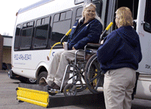 Woman in a wheelchair being lowered from bus.